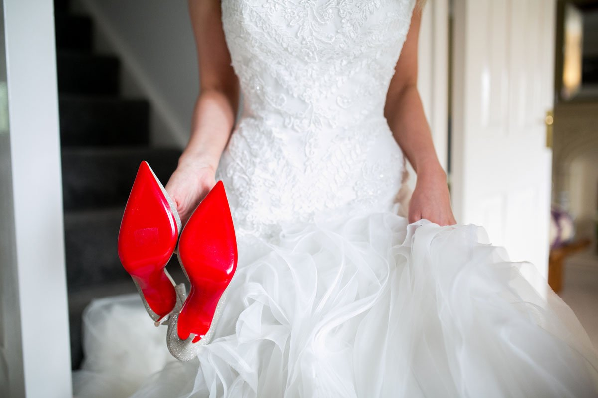 bride with holding her louboutins
