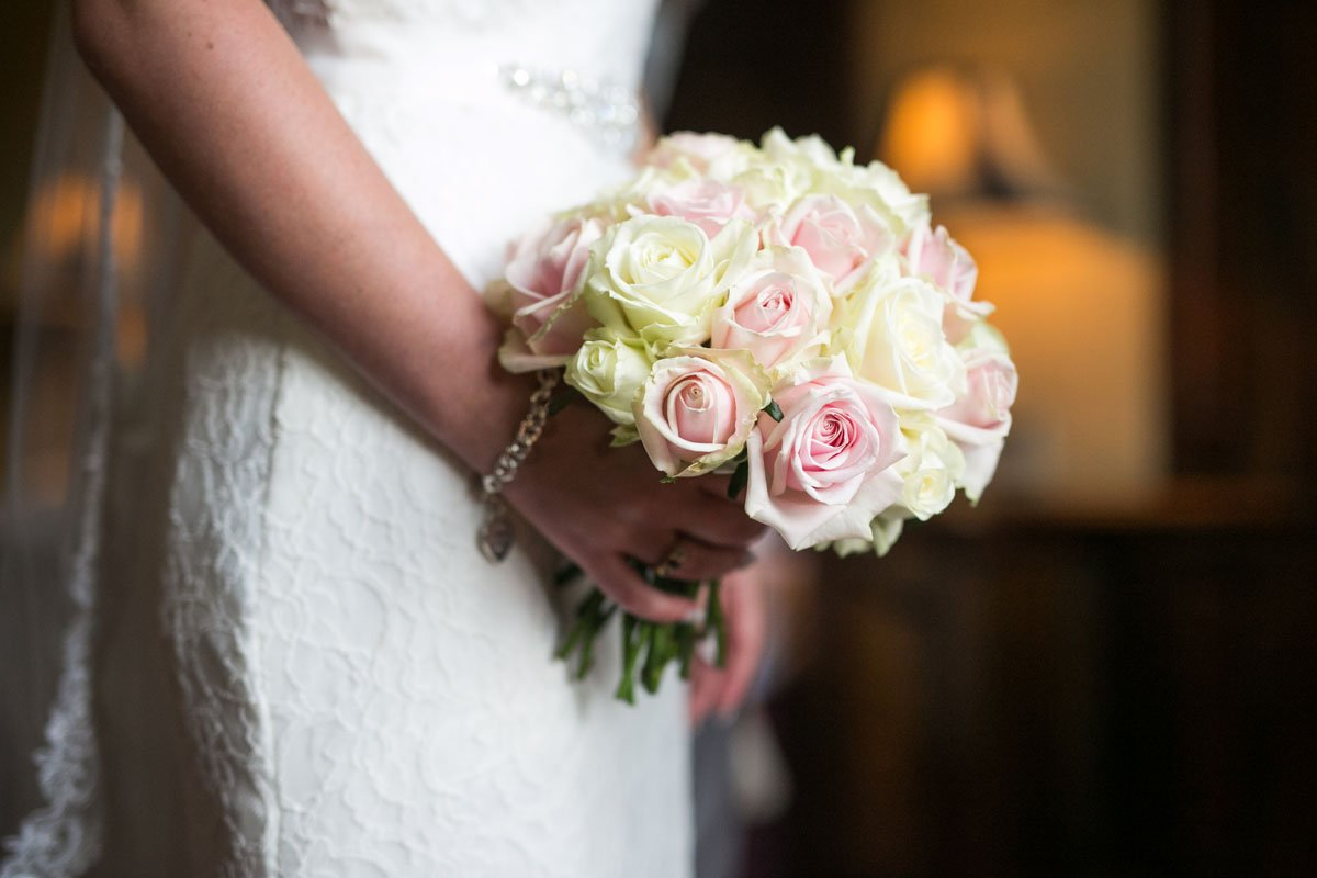 Close up shot of a bride holding a blush pink and cream bridal bouquet
