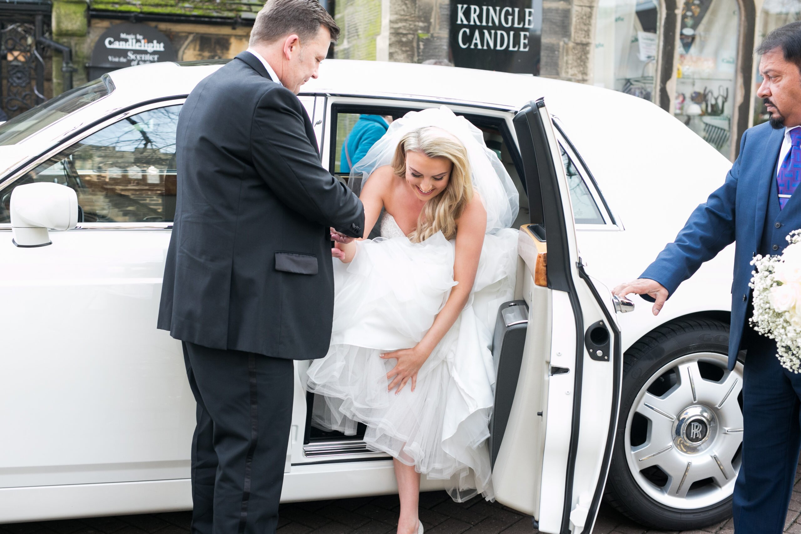 bride getting out of her rolls royce wedding car