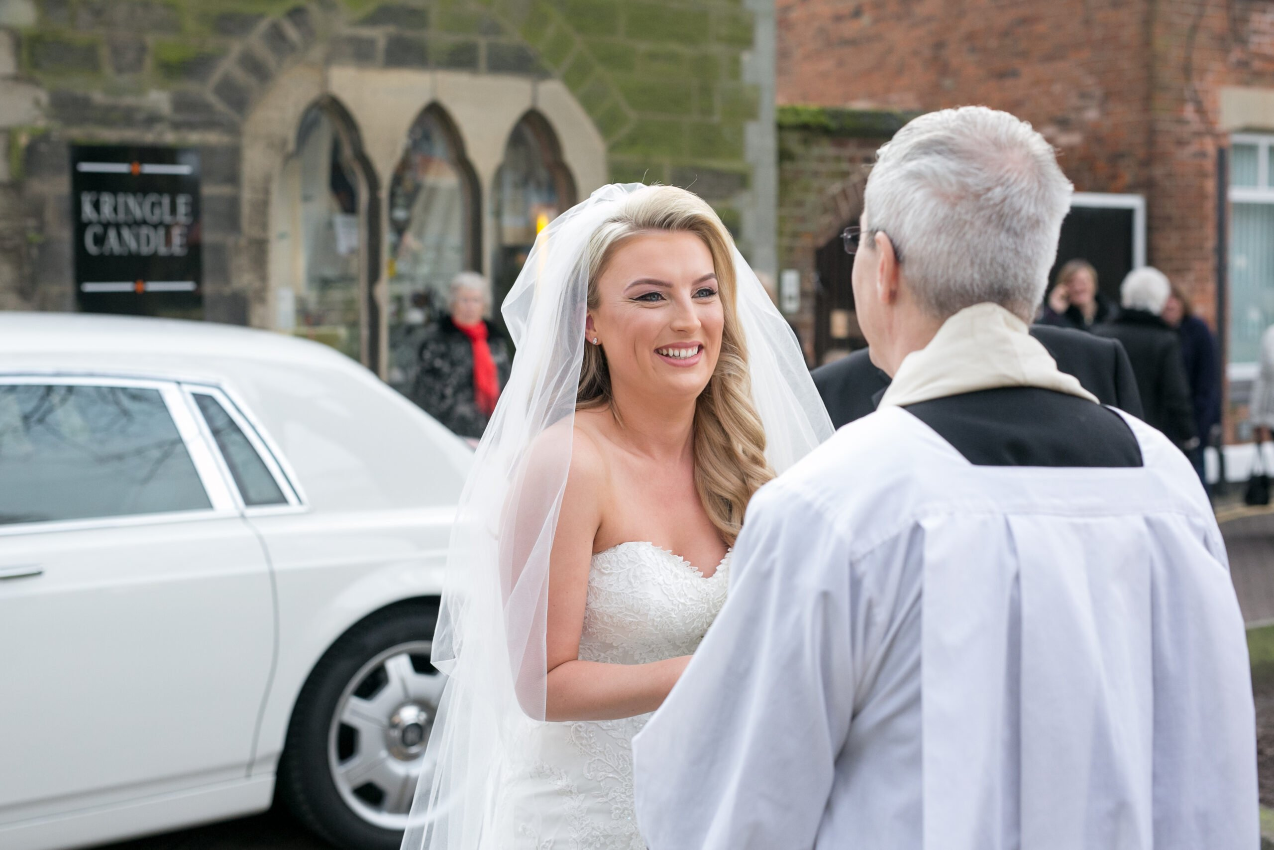 Bride speaking to the vicar at the church in the midlands