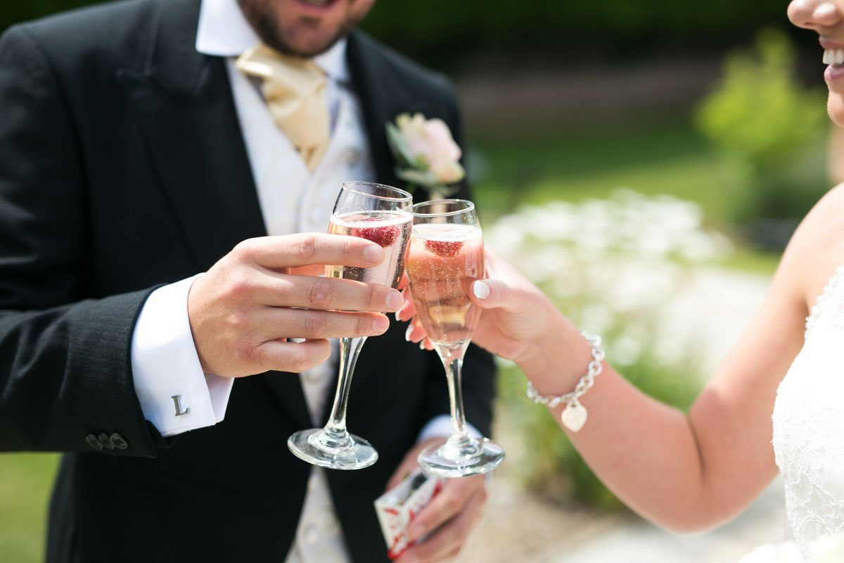 Close up shot of bride and groom toasting their glasses.