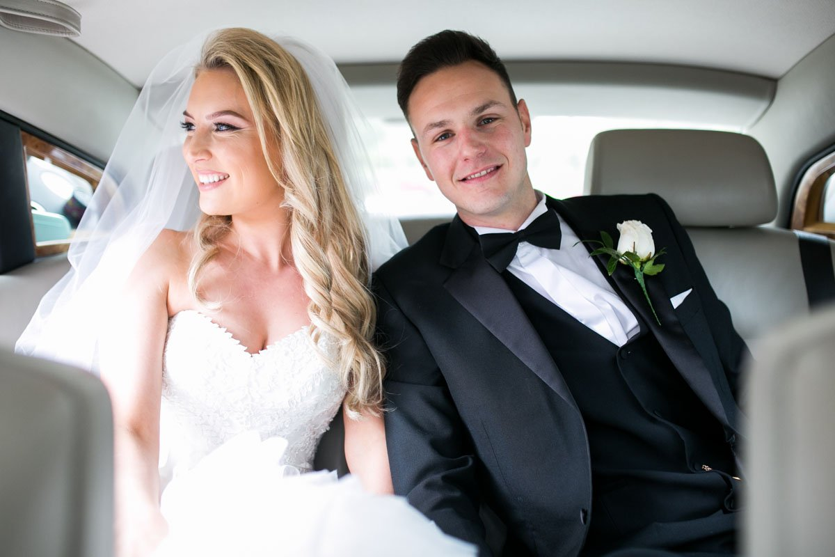 couple in the back of their wedding car