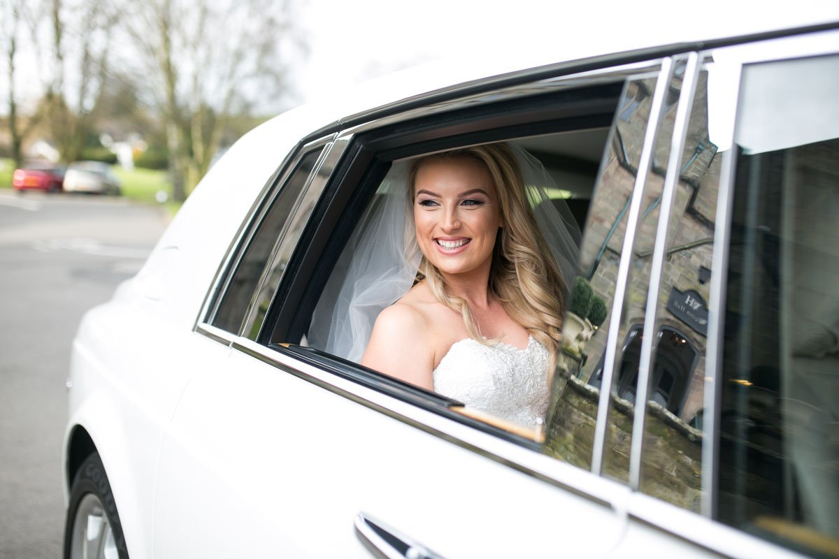 bride in the back of their wedding car