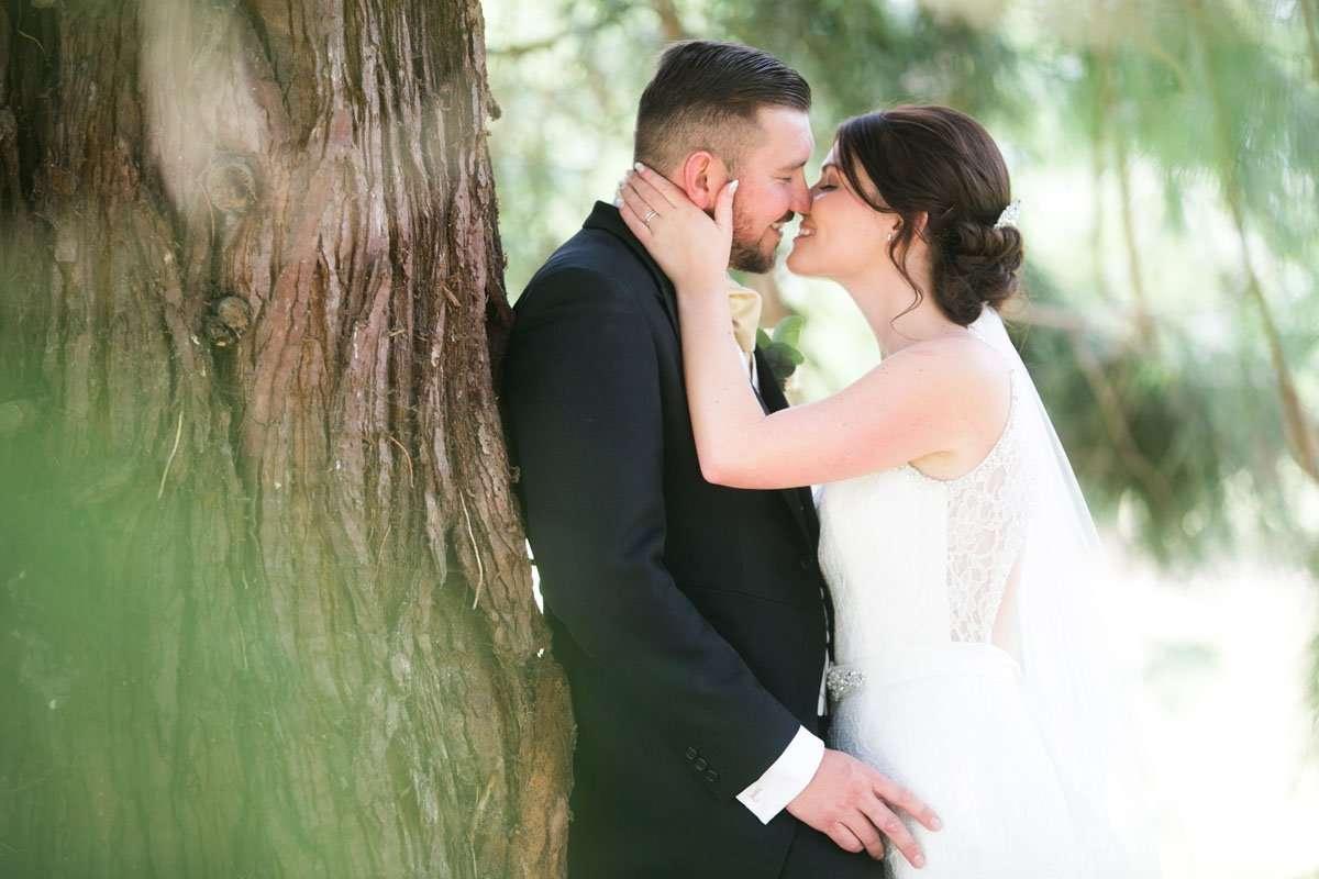 Bride kisses her groom under an oak tree