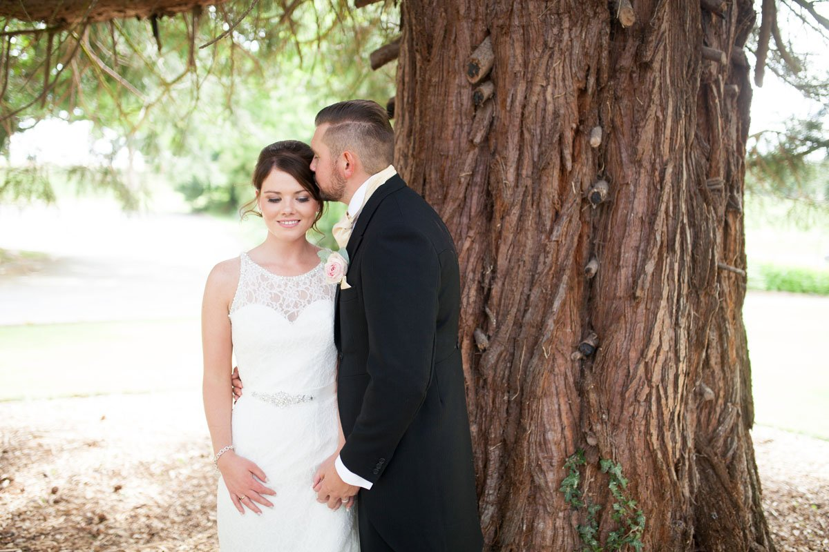 Groom kisses bride on the side of the head as they pose infront of a beautiful oak tree.
